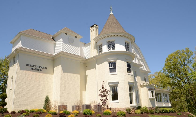 Front view of Caron's Breakthrough mansion from the exterior on a beautiful spring day.