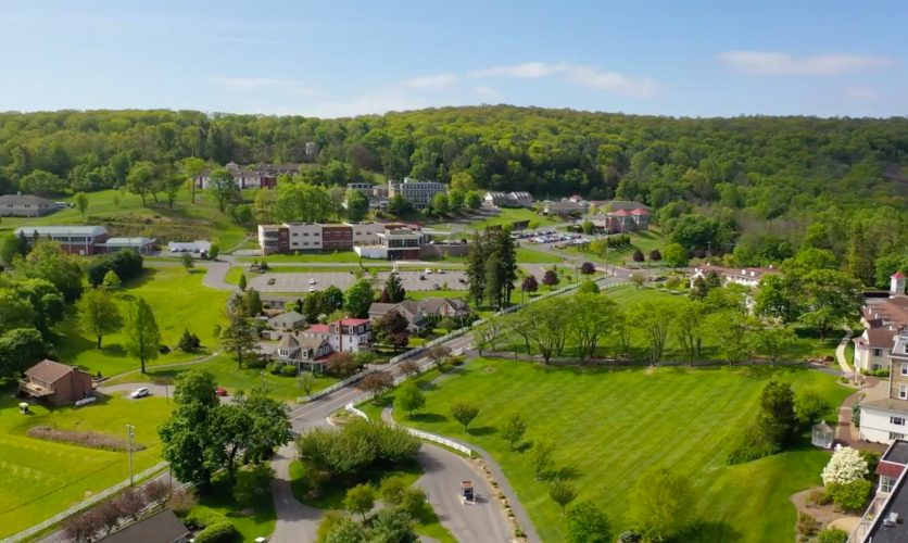 An overhead drone image above Caron Pennsylvania's campus, with rolling green hills and buildings in the distance.