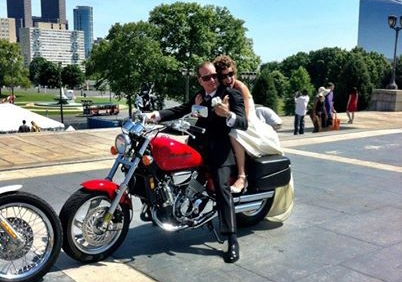 The couple riding a motorcycle on their wedding day.
