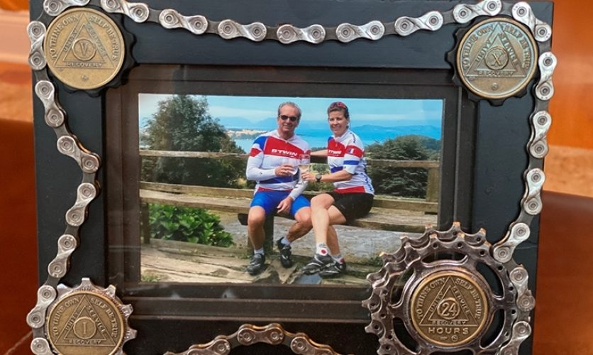 Framed photograph of William and Chantal, Caron alumni, in bike racing uniforms.