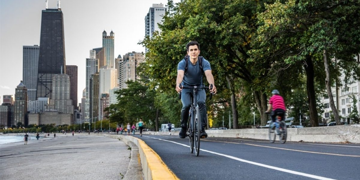 Young man riding a bike on a path with city skyline behind him.