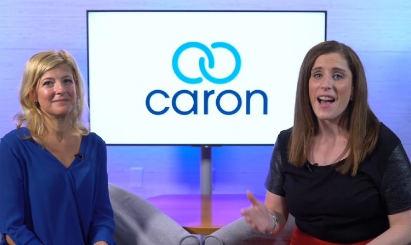 Two people, one of them Tina George, presenting in front of a screen with the Caron logo.