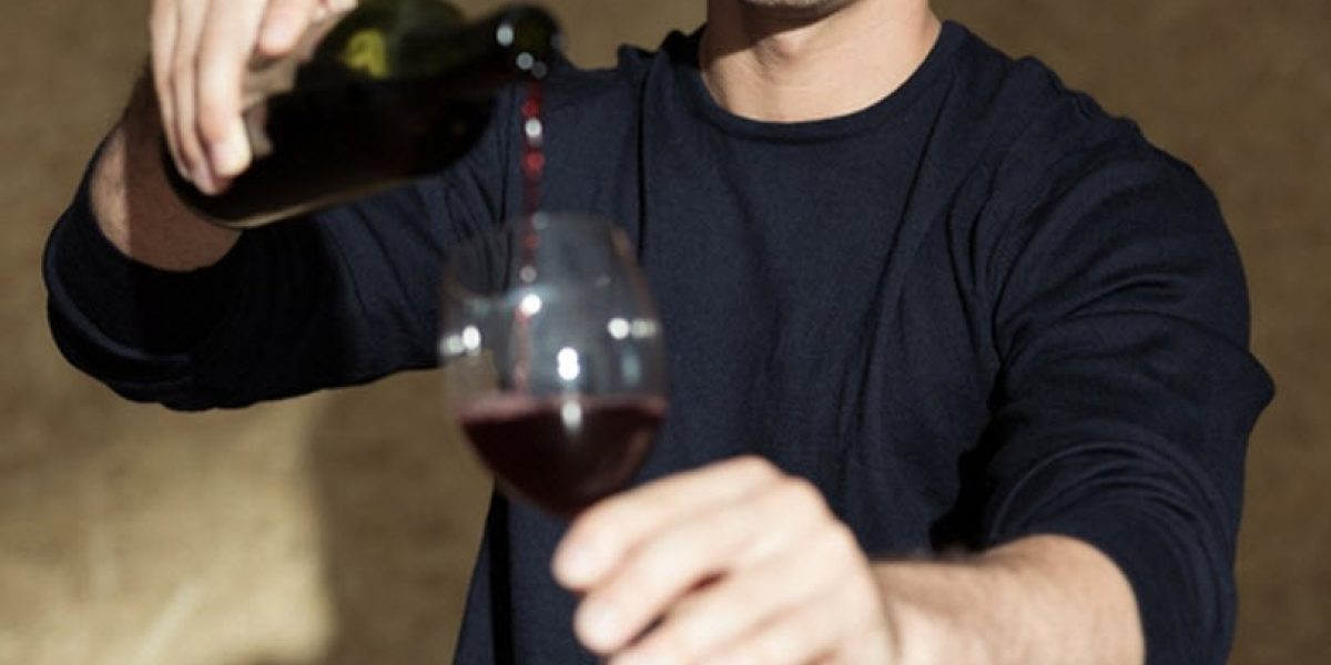 Person with their face cropped out pouring red wine into a wine glass.