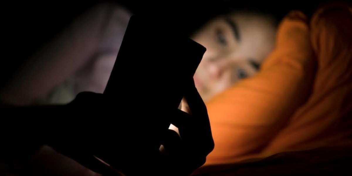 Person laying in bed in the dark, the light from their phone screen shining on their face.