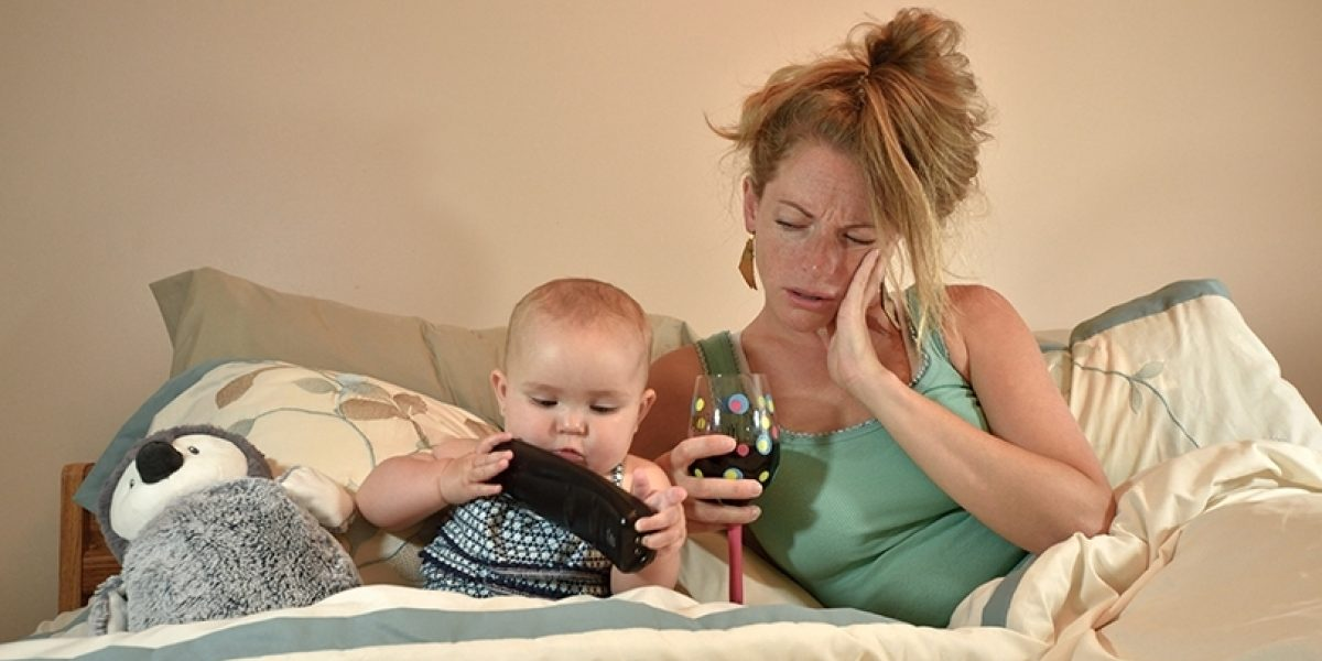 Distraught looking mother laying in bed with her baby, holding a glass of wine.