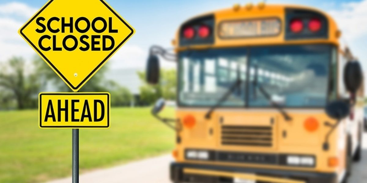 "Sign in foreground that says ""School Closed Ahead"" with an out of focus school bus in the background."
