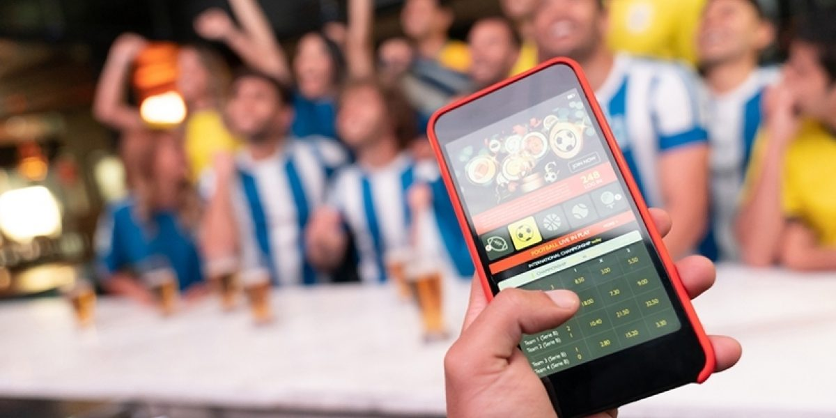 Iphone in the foreground open to a betting app, group of sports fans in the background, sitting at a bar and cheering.