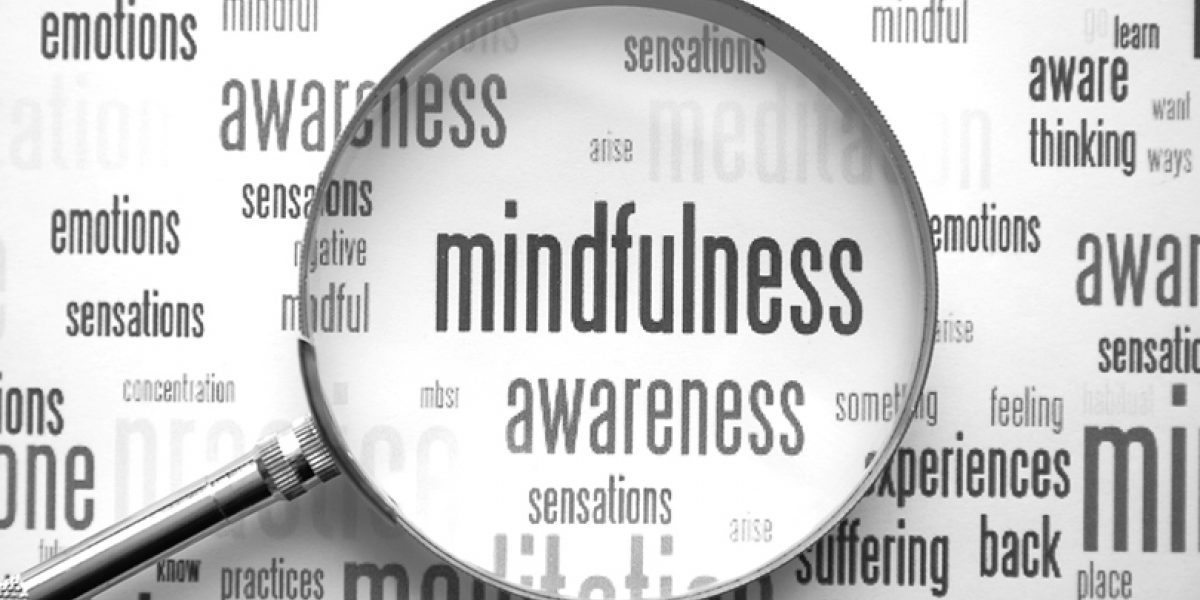 "Word cloud with a magnifying glass emphasizing the words ""mindfulness"" and ""awareness""."