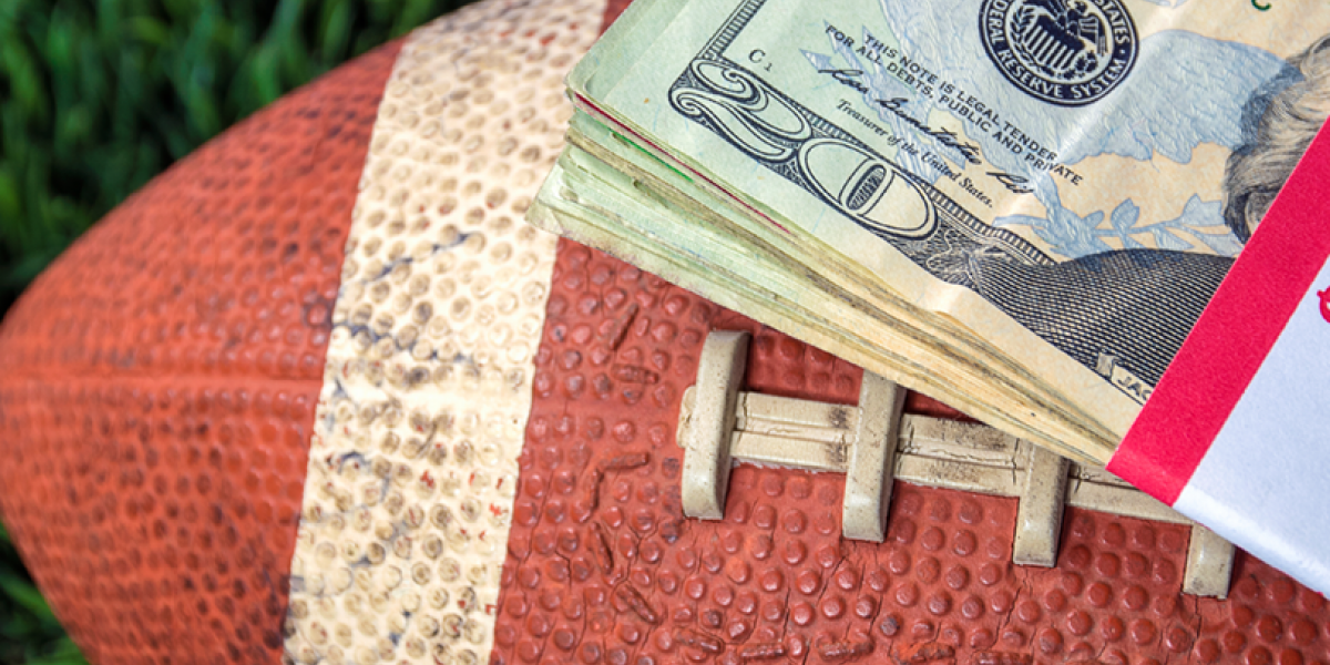 Close up of a football with a stack of twenty dollar bills.