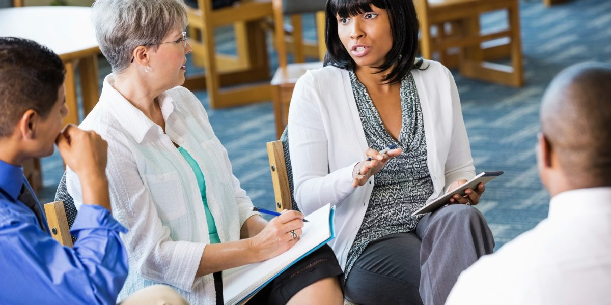 A concerned parent talking during a treatment session with a female doctor taking notes on a notebook.