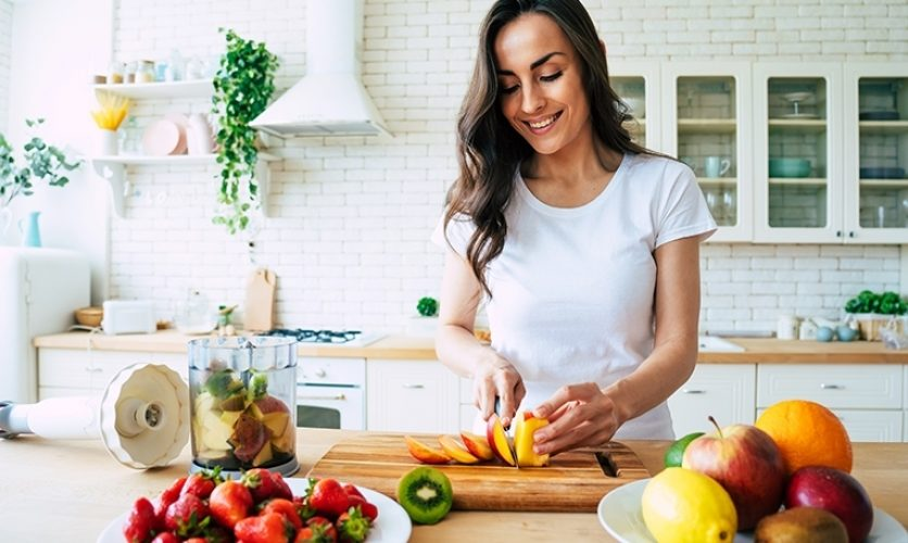 Person in well-lit, white kitchen, slicing a peach and surrounded by fresh fruit.