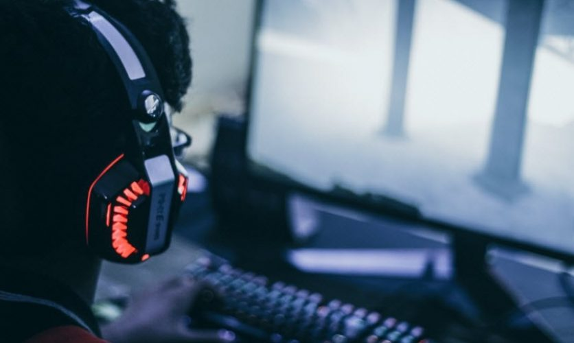 Gamer wearing light-up headset staring at computer screen.