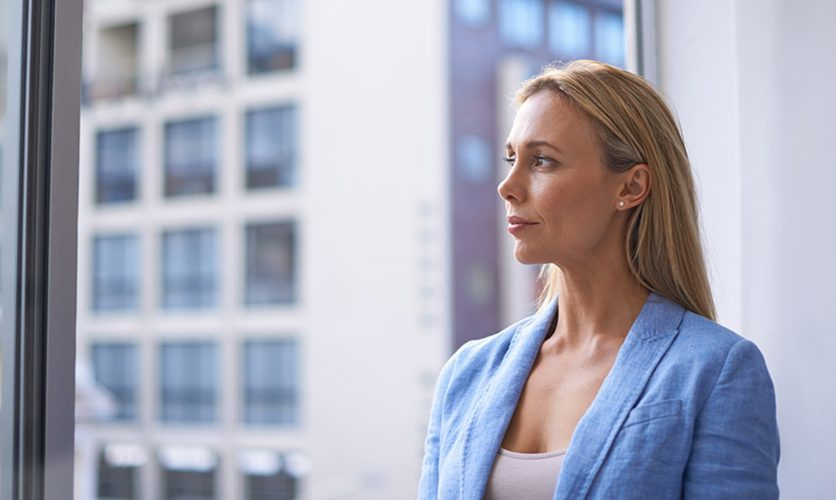 Business woman in a blue suit looking out form a glass corporate building.