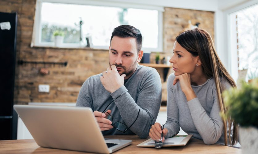 Man and woman at home looking at a the screen of a laptop on a desk.