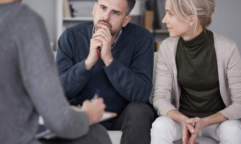 Couple sitting at a therapy session with a man in a deep gaze, while his female partner looks at him with hands folded.