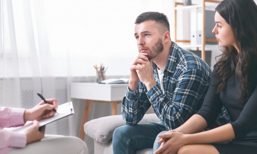 A man and a woman sitting side-by-side on a couch, looking pensively at a therapist out of view.