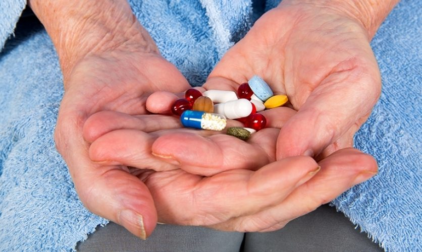 Hands of an older individual holding a colorful smattering of pills.