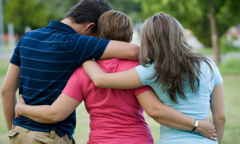 Family Comforting one another with their backs turned to the audience while outside at a park.
