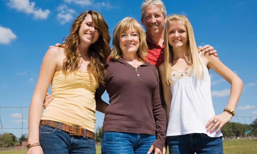 Family with mom, dad, and two daughters smiling outside in a bright vivid clear blue landscape.
