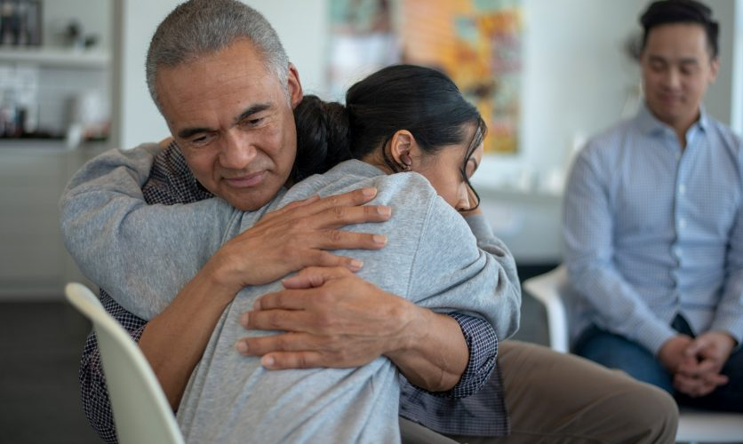 Father and daughter hugging passionately at a group treatment session.