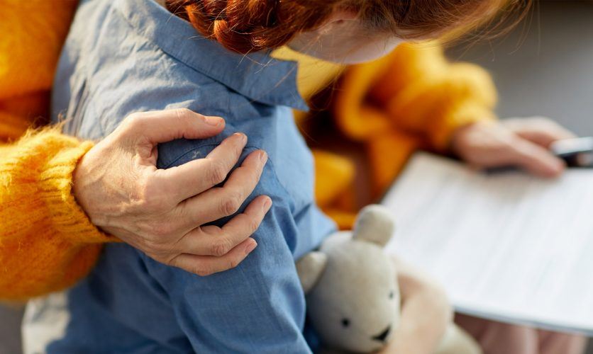 Close Up on woman's hand comforting a child's shoulders while holding a teddy bear.