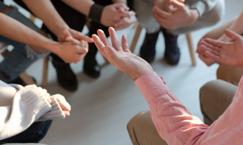 Group session with a closeup on doctors hands while sitting in a cirlce.