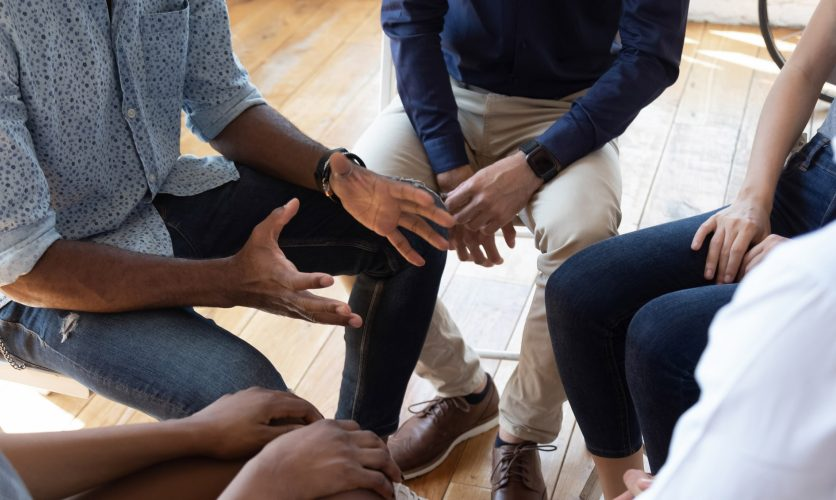 Group of people sitting in a circle with the focus on someone expressively talking with their hands open.