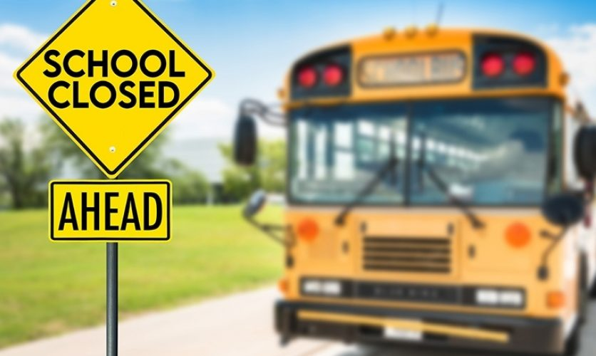 """Sign in foreground that says """"School Closed Ahead"""" with an out of focus school bus in the background."""