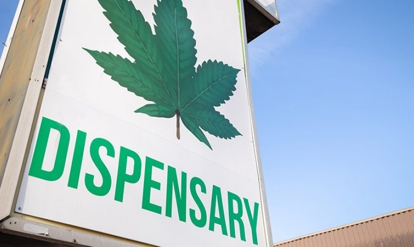 """Exterior signage showing a large marijuana leaf with the word """"dispensary"""" beneath it."""