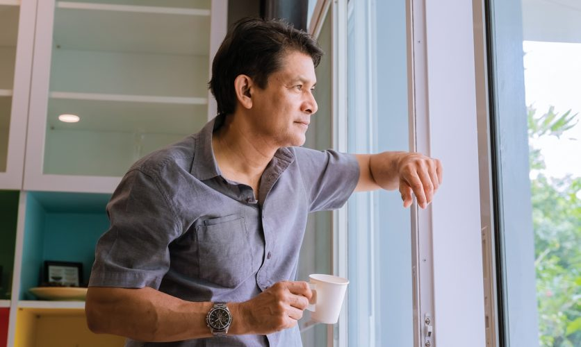 Man drinking coffee at home while gazing outdoors with his hand on the window.