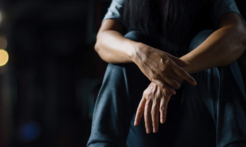 Man sitting down in a dark room with this hands crossed.