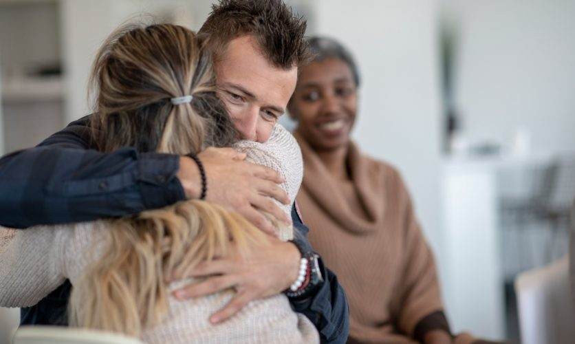 Man and woman emotionally hugging each other during a group treatment session.