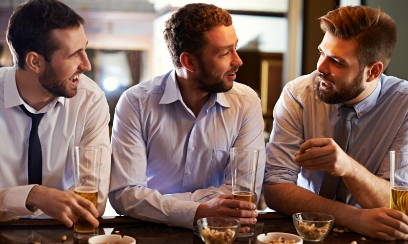 3 Men drinking beers at a bar, while talking about work.