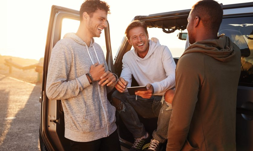 3 Diverse Men smiling next to a jeep in front of a sunset.