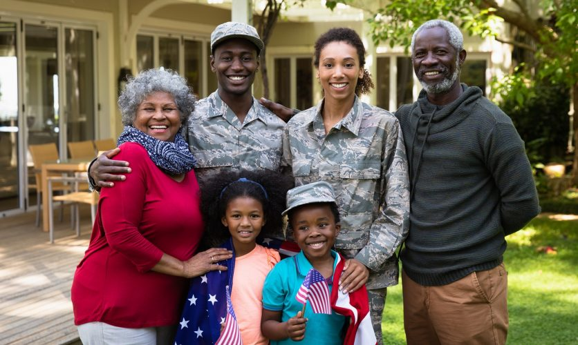 Military family with parents and children smiling outdoors on their patio space.