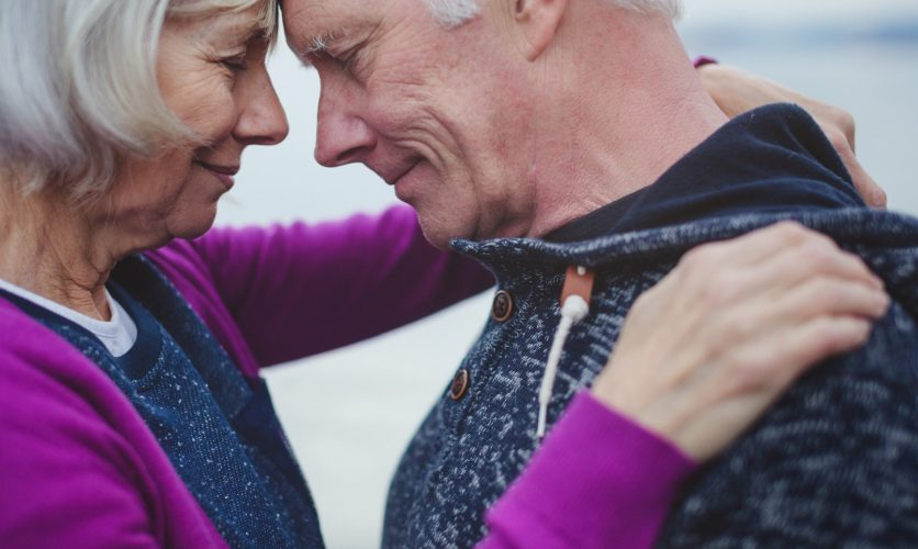 Older couple with eyes closed, hugging each other with their arms on each other's shoulders.