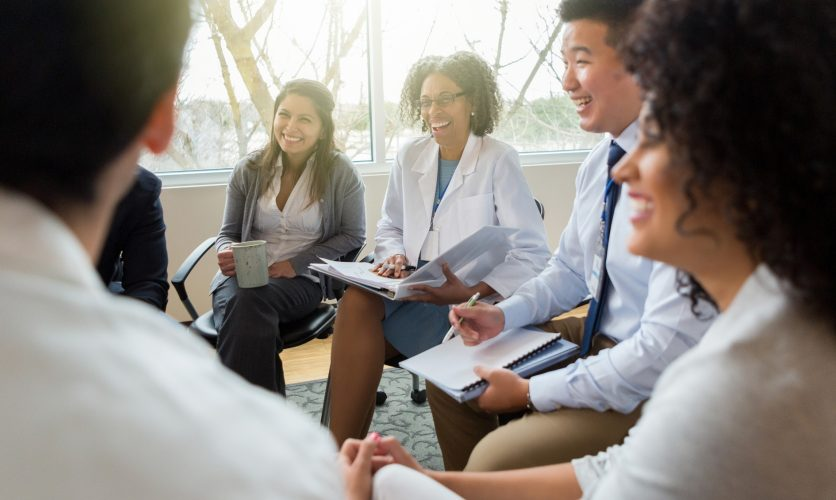 Group of physicians sitting indoors while holding notebooks and smiling.