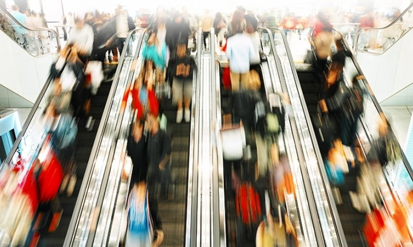 Blurred image of crowded escalators in a mall.