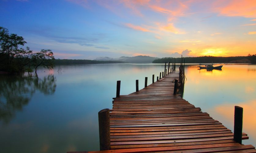 Dock overlooking a beautiful multicolored sunset.