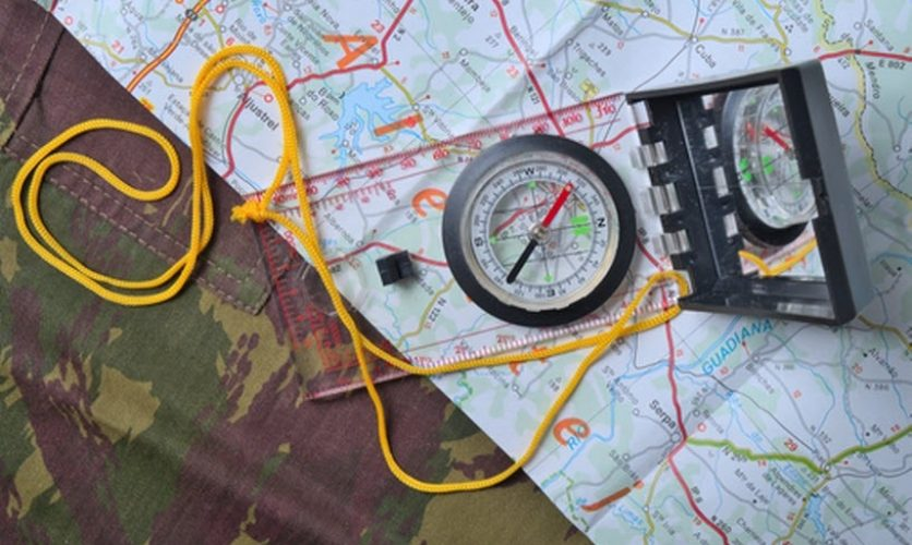 A compass sits on a paper map which is laid over camouflage fabric.