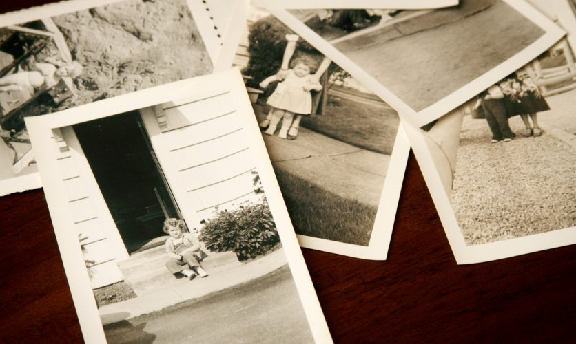 Vintage black and white photos sitting on top of a desk.