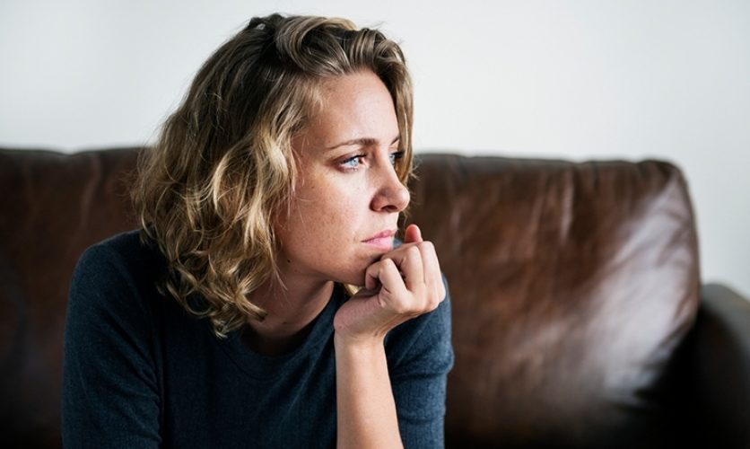 Woman sitting on a couch with her chin in her hand looking off thoughtfully.