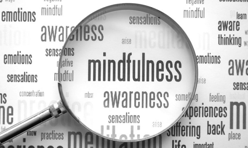 """Word cloud with a magnifying glass emphasizing the words """"mindfulness"""" and """"awareness""""."""