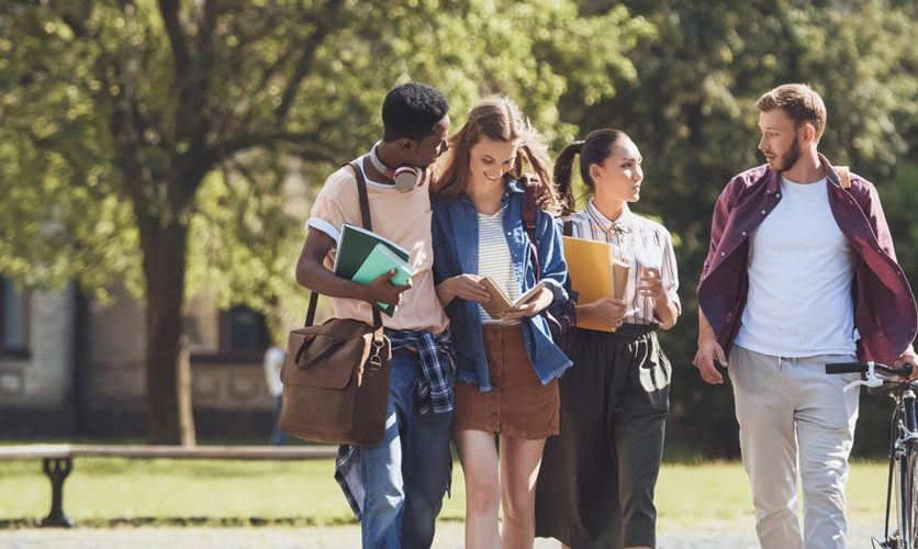 Diverse group of teenagers walking on a collage campus.