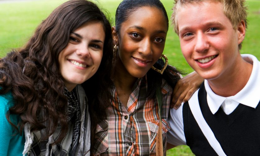 3 diverse teenagers smiling outdoors at a park.