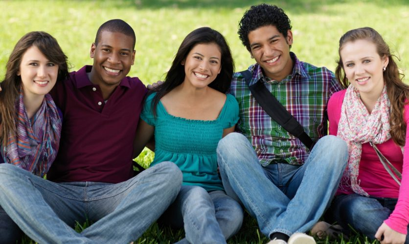 5 Diverse teenagers sitting on the lawn while smiling.