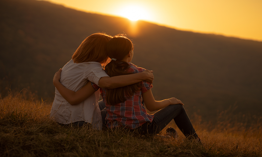 Parent and adult child sitting in a field at sunset with their arms around each other.