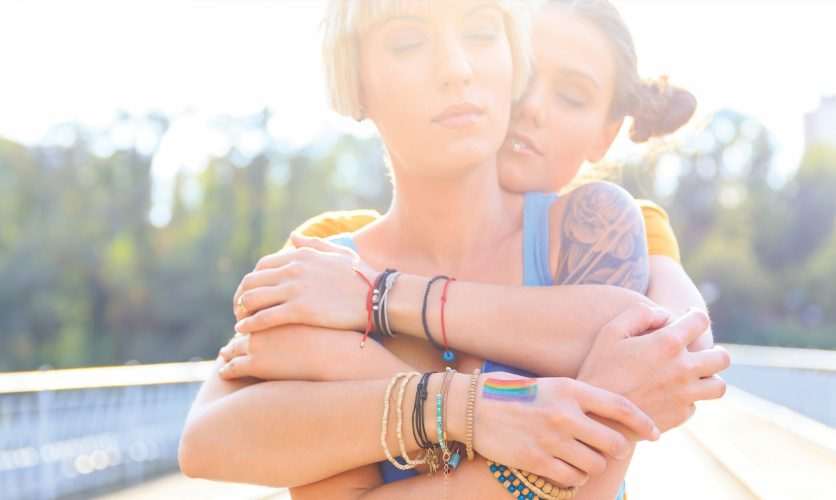 Two girls lgbtq hugging outdoors on a bridge in front of a sunset.