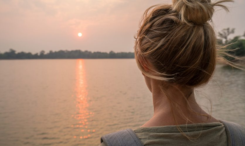 Woman with back turned overlooking a sunset over a lake.