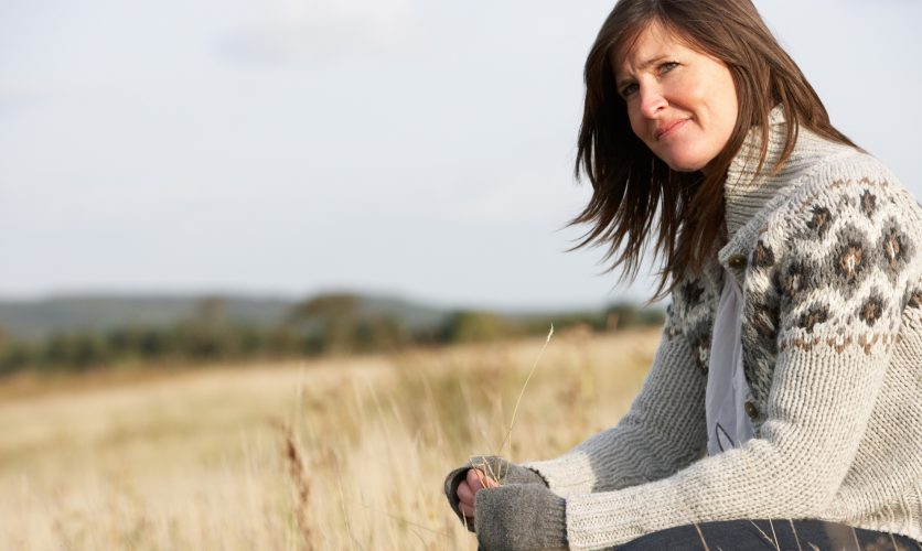 Woman sitting outdoors in a grey sweater in the landscape looking afar.